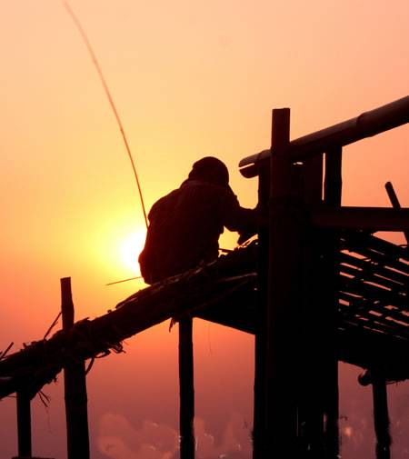 A worker is operating on the building roof.