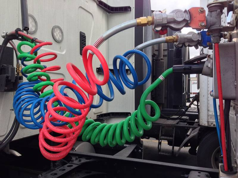There are three recoiled air brake hoses with red, blue and green color.